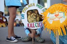 """Una niña sostiene un cartel a las afueras de la clínica dental  River Bluff, de Walter James Palmer el acusado de matar al león """"Cecil"""" en Zimbabue, en Bloomington, EEUU, jul 29 2015. La Asamblea General de Naciones Unidas llamó el jueves a todos los países a que intensifiquen sus esfuerzos para enfrentar la caza ilegal y el tráfico de fauna silvestre, en medio del escándalo desatado por la matanza del león """"Cecil"""" en Zimbabue.  REUTERS/Eric Miller"""