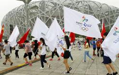 Participants holding Chinese national flags and Beijing 2022 Olympic flags walk past the Birds' Nest, also known as the National Stadium, to attend a rehearsal of a performance in Beijing, China, July 30, 2015. REUTERS/China Daily