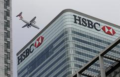 A Swiss International aircraft flies past the HSBC headquarters building in the Canary Wharf financial district in east London in this February 15, 2015 file photo.  REUTERS/Peter Nicholls/Files