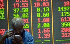 An investor checks on his mobile phone in front of an electronic board showing stock information at a brokerage house in Hangzhou, Zhejiang province, China, July 29, 2015.  REUTERS/Stringer
