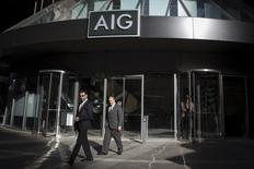 People exit the AIG building in New York's financial district March 19, 2015. American International Group Inc shareholders will seek final approval of $970.5 million in settlements resolving claims the company misled investors ahead of the 2008 financial crisis. AIG has agreed to pay $960 million, while its auditors at Price Waterhouse Coopers have agreed to pay $10.5 million.  REUTERS/Brendan McDermid             TPX IMAGES OF THE DAY - RTR4U3F2