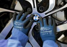 A worker mounts the logo on a rim at the serial production BMW i3 electric car in the BMW factory in Leipzig September 18, 2013.  REUTERS/Fabrizio Bensch (GERMANY - Tags: TRANSPORT) - RTX13PUE