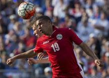Jul 18, 2015; Baltimore, MD, USA; Cuba midfielder Yasmany Lopez (19) heads the ball past United States forward Aron Johannsson (9) during a CONCACAF Gold Cup quarterfinal match at M&T Bank Stadium. The United States won 6-0. Mandatory Credit: Bill Streicher-USA TODAY Sports