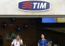 Una mujer habla por celular junto a una empleada de Telecom Italia Mobile (TIM) en una de sus tiendas en el centro de Río de Janeiro, 20 de agosto de 2014. TIM Participações SA, la segunda mayor empresa de telefonía inalámbrica de Brasil, reportó el martes una caída de un 20 por ciento en sus ganancias trimestrales ajustadas debido a la debilidad de las ventas. REUTERS/Pilar Olivares