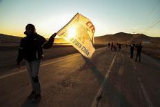 """Las protestas de trabajadores tercerizados y la ocupación ilegal de algunas minas de la estatal Codelco han provocado pérdidas por al menos unos 15 millones de dólares, dijo el miércoles la compañía, aunque las cifras podrían aumentar ante nulas señales de un pronto fin del conflicto. En la imagen, una mujer sostiene una bandera que dice """"Cobre para Chile"""", durante una protesta en el lugar donde murió un trabajador de Codelco, en la minera de cobre El Salvador, en El Salvador, Chile. 24 julio 2015. REUTERS/Francisco Fuentes"""