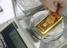 Работник предприятия Красцветмет взвешивает слиток золота. Красноярск, 25 февраля 2013 года. Золотовалютные резервы РФ сократились до $357,6 миллиарда, потеряв за неделю с 24 по 31 июля $1,7 миллиарда, следует из данных Банка России. REUTERS/Ilya Naymushin