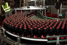 Trois embouteilleurs européens de Coca-Cola ont décidé de fusionner dans l'espoir de voir l'effet de taille et des économies de coûts relancer les ventes des boissons non alcoolisées fabriquées par le géant américain. /Photo d'archives/REUTERS/Jacky Naegelen