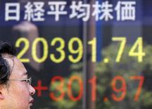 Un hombre camina junto a un tablero electrónico que muestra el índice Nikkei de Japón, afuera de una correduría en Tokio, 14 de julio de 2015.  Las bolsas de Asia rebotaban el viernes desde unos mínimos iniciales, pero se encaminan a su tercera caída semanal consecutiva, mientras el dólar subía antes de unos datos de empleo en Estados Unidos que podrían llevar a la Reserva Federal a elevar las tasas de interés en septiembre. REUTERS/Toru Hanai