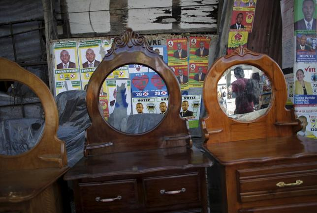 Posters of candidates running for legislative elections are plastered on a wall behind furniture on display for sale on a street in Port-au-Prince, Haiti, August 7, 2015. REUTERS/Andres Martinez Casares
