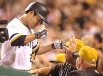 Aug 9, 2015; Pittsburgh, PA, USA; Pittsburgh Pirates third baseman Jung Ho Kang (27) celebrates at the dugout after hitting a three run home run against the Los Angeles Dodgers during the seventh inning at PNC Park. Charles LeClaire-USA TODAY Sports