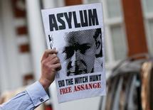 Un partidario de Julian Assange sostiene un afiche con su rostro a las afueras de la embajada de Ecuador en Londres, jun 19 2015. Ecuador negó el lunes haber pedido a Suecia una garantía de asilo para el fundador de WikiLeaks como condición para permitir que fiscales de ese país interroguen a Julian Assange en Londres.  REUTERS/Stefan Wermuth