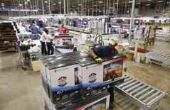 Un trabajador empacando televisores en una bodega de Element Electronics en Winnsboro, EEUU, mayo 29 2014. Los inventarios mayoristas de Estados Unidos subieron más de lo previsto en junio, en el más reciente indicio de que la economía creció en el segundo trimestre a un ritmo más veloz de lo reportado el mes pasado. REUTERS/Chris Keane