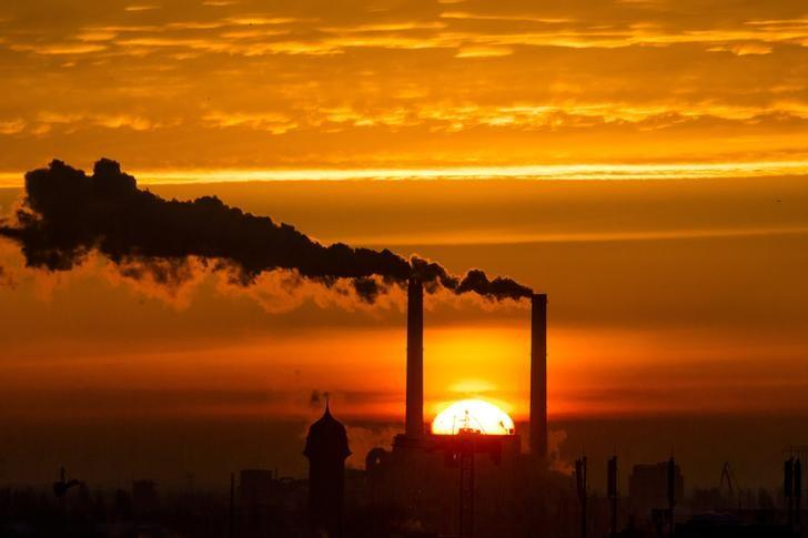 The sun rises behind the billowing chimneys of a power station in Berlin, November 27, 2013.   REUTERS/Thomas Peter