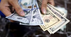Работник банка проверяет подлинность долларовых купюр. Ханой, 12 августа 2015 года. Доллар в четверг держится выше месячного минимума к корзине валют, так как падение юаня замедлилось, смягчив опасения о том, что Китай пытается резко девальвировать валюту, чтобы получить конкурентное преимущество. REUTERS/Kham