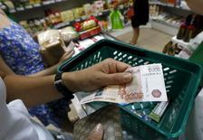 Покупательница расплачивается 5-тысячной купюрой в продуктовом магазине в Красноярске. 6 августа 2015 года. Четвертый по выручке в РФ ритейлер Дикси сообщил в четверг, что увеличил продажи на 11,6 процента в июле 2015 года в годовом выражении, продолжив замедление темпов роста. REUTERS/Ilya Naymushin