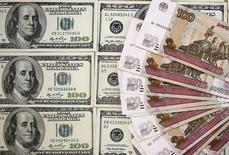 Рублевые и долларовые купюры в Сараево 9 марта 2015 года. Рубль ушел в существенный минус к вечеру четверга вслед за нефтью, а также отражая спрос на валюту, который может формироваться как валютной конверсией полученных ранее рублевых дивидендов, так и рыночным позиционированием в ожидании напряженного графика выплат по внешнему долгу в конце года. REUTERS/Dado Ruvic