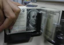 Un empleado bancario cuenta dólares estadounidenses en el banco Kasikornbank en Bangko, 21 de enero de 2010. La economía de Estados Unidos se encamina a crecer un 0,7 por ciento en el tercer trimestre ya que un alza en las ventas minoristas en julio no fue suficiente para superar una esperada caída en los inventarios, mostró el jueves el modelo de predicciones GDPNow de la Reserva Federal de Atlanta. REUTERS/Sukree Sukplang