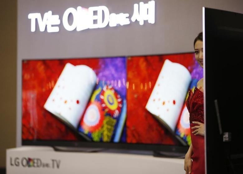 A model poses in front of LG Electronics' flexible organic light-emitting diode (OLED) TV sets, which are made with LG Display flat screens, during the 2014 Korea Electronics Show in Goyang October 17, 2014. REUTERS/Kim Hong-Ji