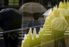 Peatones se reflejan en un tablero electrónico que muestra la gráfica de fluctuación del índice Nikkei de Japón, afuera de una correduría en Tokio, Japón, 17 de agosto de 2015. La Bolsa de Tokio avanzó el lunes después de unos datos que mostraron que la contracción económica japonesa fue menos severa de lo previsto. REUTERS/Yuya Shino