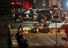 Сотрудники служб безопасности Таиланда на месте взрыва в центре Бангкока 17 августа 2015 года. Взрыв мотоцикла у индуистского храма Эраван в центре Бангкока унес жизни по меньшей мере 27 человек, часть из них - иностранцы, сообщили местные СМИ в понедельник.  REUTERS/Chaiwat Subprasom