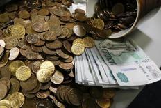 Рублевые купюры и монеты в офисе частной компании в Красноярске 6 ноября 2014 года. Рубль обновил полугодовой минимум при открытии торгов среды, но не прошел уровень 66 за доллар, вокруг которого, по оценкам участников рынка, значительное предложение валюты от корпораций-экспортеров.  REUTERS/Ilya Naymushin