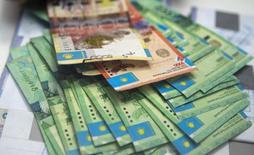 Купюры валюты тенге в отделении Евразийского банка в Алма-Ате 15 января 2015 года. Казахстанский тенге на межбанке после основной торговой сессии приблизился к верхней границе коридора и торгуется по 196,83-197,13 тенге за $1. Аналитики говорят о контролируемой девальвации и ждут установления нового обменного курса тенге к концу торгового дня. REUTERS/Shamil Zhumatov