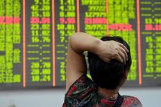 Un inversor mira un tablero electrónico que muestra la información de las acciones, en una correduría en Hangzhou, China, 18 de agosto de 2015. Los mercados de acciones chinas sufrieron fuertes altibajos el miércoles, con un desplome inicial y un repunte posterior en una sesión que subrayó que los inversores casi no tienen fe en los esfuerzos de estabilización financiera que lanzó el gobierno hace un mes. REUTERS/China Daily