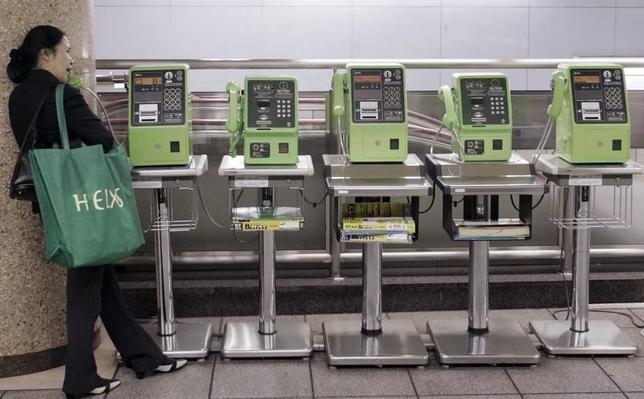 """8月20日、1世紀以上にわたり国民生活を支えてきた固定電話の""""終わり""""が始まろうとしている。写真は都内の駅構内で公衆電話を使う女性。2007年5月撮影(2015年 ロイター/Kim Kyung-Hoon)"""