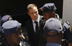 South African Olympic and Paralympic sprinter Oscar Pistorius (C) is escorted to a police van after his sentencing at the North Gauteng High Court in Pretoria October 21, 2014.  REUTERS/Siphiwe Sibeko/Files