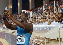Justin Gatlin of the U.S. takes a selfie with supporters after winning the 100 meters men event at the IAAF Diamond League Herculis meeting at the Louis II Stadium in Monaco, July 17, 2015. REUTERS/Jean-Pierre Amet
