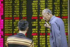 Inversores hablan frente a un tablero electrónico que muestra la información de las acciones en una correduría en Beijing, China, 21 de agosto de 2015. Los mercados accionarios chinos perdieron más de un 4 por ciento el viernes y sus principales índices sufrieron un declive semanal de casi 12 por ciento, lo que generó dudas sobre la capacidad de Pekín para evitar otra corriente vendedora en las bolsas causada por el pánico de los inversores. REUTERS/Stringer