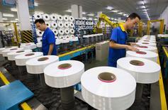 Unos trabajadores en la línea de producción de una planta textil en Suzhou el 13 de junio de 2015. La actividad del sector manufacturero de China se contrajo en agosto a su mayor ritmo en casi seis años y medio, debido a la debilidad de la demanda doméstica y de las exportaciones, mostró un sondeo privado, lo que aumentó los temores de que la segunda mayor economía mundial se esté desacelerando con fuerza. REUTERS/China Daily