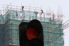 Trabajadores vistos detrás de un semáforo en una construcción de un edificio de negocios, en Beijing, 12 de julio de 2013. Las señales de que la desaceleración en China se está profundizando y un débil crecimiento reportado el viernes en Europa y Estados Unidos dañaron aún más al panorama para la economía global, lo que hizo que los precios de las acciones y las materias primas se derrumbaran. REUTERS/Kim Kyung-Hoon