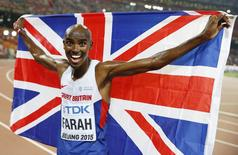 Mo Farah of Britain holds the Union Jack flag as he celebrates winning the men's 10,000 metres final at the 15th IAAF World Championships at the National Stadium in Beijing, China August 22, 2015.        REUTERS/Phil Noble
