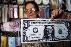 Mulher segura nota gigante de dólar e uma nota de 5 reais em Itu. 06/08/2015 REUTERS/Nacho Doce