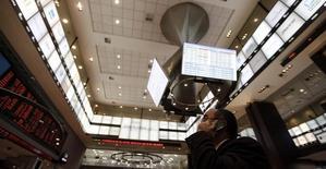 Homem no telefone enquanto olha para monitores com cotações, em São Paulo.  04/08/2011   REUTERS/Nacho Doce