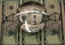 Billetes de 5 dólares en una ilustración fotográfica, tomada en Washington, 14 de abril de 2015. El dólar repuntaba un 1 por ciento el martes frente a una canasta de destacadas monedas y rebotaba desde mínimos de siete meses frente al yen y el euro, después de que los activos más riesgosos recibieron un impulso por la baja de tasas de interés del banco central de China. REUTERS/Gary Cameron
