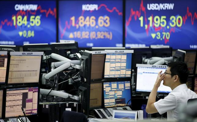 A currency dealer works in front of electronic boards showing the Korea Composite Stock Price Index (KOSPI) (C), the exchange rates between the Chinese yuan and South Korean won (L), and tthe exchange rate between U.S. dollar and South Korean won (R), at a dealing room of a bank in Seoul, South Korea, August 25, 2015.   REUTERS/Kim Hong-Ji