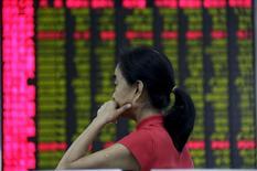 Una inversora mira un tablero electrónico que muestra la información de las acciones en una correduría en Beijing, 26 de agosto de 2015. Los principales índices bursátiles de China abrieron con ganancias el miércoles, después de las agresivas medidas de flexibilización de política monetaria anunciadas por el banco central en la tarde del martes, luego de un fuerte hundimiento del mercado. REUTERS/Jason Lee