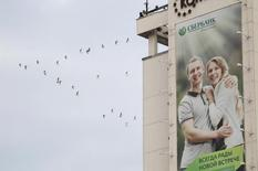 Рекламный плакат Сбербанка на здании в Ставрополе. 11 декабря 2014 года. Крупнейший госбанк РФ Сбербанк во втором квартале 2015 года сократил чистую прибыль на 44 процента в годовом выражении, увеличив расходы на резервы на фоне рецессии в экономике, но превысил ожидания аналитиков, которые прогнозировали 41,2 миллиарда рублей благодаря заработкам на валюте и трейдинге. REUTERS/Eduard Korniyenko