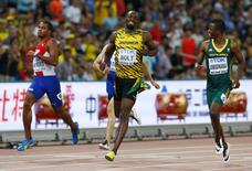 Usain Bolt of Jamaica (C) runs past Roberto Skyers of Cuba and Anaso Jobodwana of South Africa (R) to win their men's 200 metres semi-final at the IAAF World Championships at the National Stadium in Beijing, China August 26, 2015.    REUTERS/David Gray