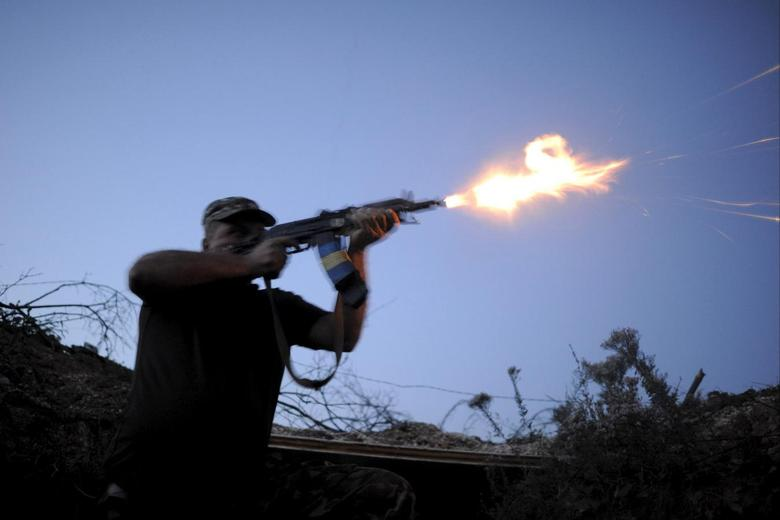 A serviceman of the Ukrainian armed forces fires a weapon in the direction of positions of units of the armed forces of the self-proclaimed Donetsk People's Republic during a battle in Avdiivka, Donetsk region, Ukraine, August 23, 2015.   REUTERS/Maksim Levin