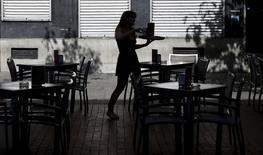 La economía española registró un crecimiento intertrimestral del Producto Interior Bruto (PIB) del 1 por ciento en el segundo trimestre, su mayor tasa de crecimiento en los últimos ocho años, según datos del Instituto Nacional de Estadística (INE). En la imagen, una camarera prepara lsa mesas en una terraza en Madrid, el  26 de agosto de 2015. REUTERS/Sergio Pérez