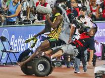 Usain Bolt of Jamaica is hit by a cameraman on a Segway as he celebrates after winning the men's 200 metres final at the 15th IAAF World Championships at the National Stadium in Beijing, China, August 27, 2015. REUTERS/Stringer