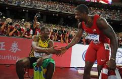 Usain Bolt of Jamaica (L) shakes hands with Justin Gatlin from the U.S. as he poses for photographers after winning the men's 200 meters final during the 15th IAAF World Championships at the National Stadium in Beijing, China, August 27, 2015.         REUTERS/Kai Pfaffenbach