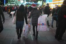 Women make their way though Times Square with bags of purchases from Toys R Us in New York November 27, 2014. REUTERS/Carlo Allegri