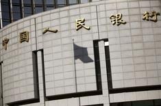 La sombra de la bandera nacional china en la sede del banco central del país, en el centro de Pekín, 24 de noviembre de 2014. El banco central de China planea endurecer las normas sobre los contratos de divisas a plazo a partir de octubre, dijeron a Reuters fuentes con conocimiento directo del asunto, en un intento por frenar la especulación y la volatilidad tras una devaluación sorpresiva de la moneda el mes pasado. REUTERS/Kim Kyung-Hoon/FIles