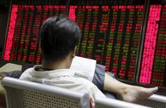Un inversor mira un diario frente a un tablero electrónico en una correduría en Beijing, 27 de agosto de 2015. Las acciones chinas consiguieron frenar fuertes pérdidas y cerraron la sesión del miércoles casi estables, luego de que medidas de respaldo de corredurías locales disiparon los temores de los inversores de que Pekín esté intensificando sus esfuerzos contra las operaciones informales de financiamiento. REUTERS/Jason Lee