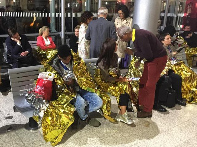Passengers wrapped in thermal foil blankets given out by emergency services after their Eurostar train was stranded at Calais Station, after intruders were seen near the Eurotunnel, in Calais, France September 2, 2015. REUTERS/John Pullman