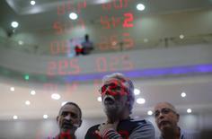 Consumidores reagem ao ver a cotação do dólar em relação ao real e de outras moedas num painel de uma casa de câmbio no Rio de Janeiro. 26/08/2015 REUTERS/Ricardo Moraes